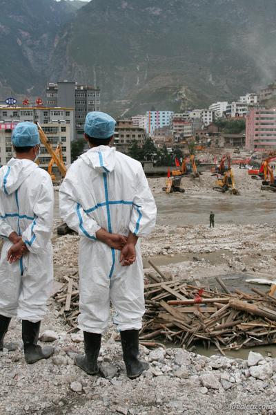 两位消杀人员站在白龙江边,看河床上清淤的部队作业